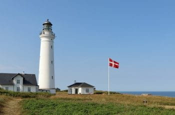 A lighthouse in Denmark with the Danish flag outside.