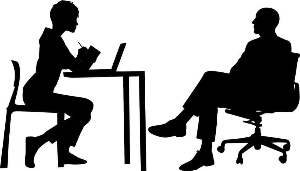 Black and white silhouettes of figures on either side of a desk, discussing.