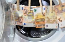 Euro notes, hung up in front of a washing machine.