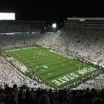 Penn State university football stadium during game at night.