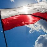 Polish flag flutters in the breeze against a blue sky.