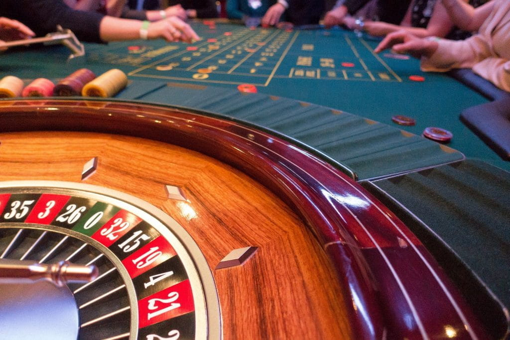 A roulette wheel sits still while gamblers sit at the opposite end of the table.