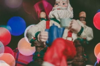 A festive Santa Claus figurine in front of twinkling Christmas lights.