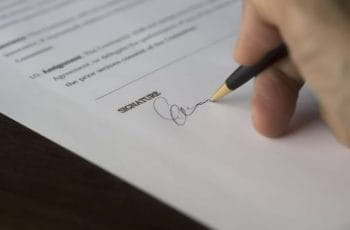 A white hand signs a contract.