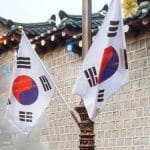 South Korea flags next to a traditional building.