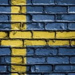 The Swedish flag painted on a brick wall.