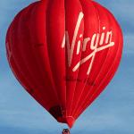 A Virgin red hot air balloon in a bright blue sky.