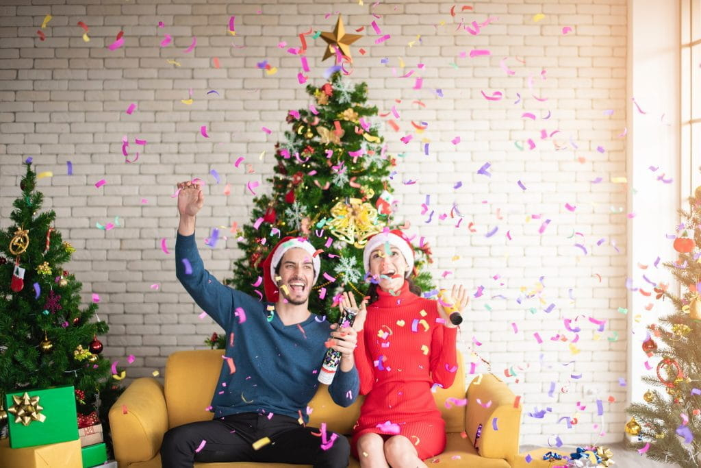 A man and a woman sit on a sofa celebrating Christmas, with decorated trees in the background and colorful confetti falling down.