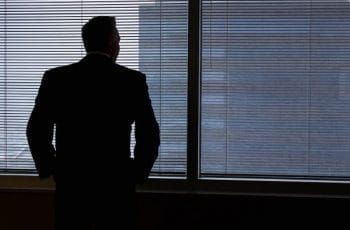 A silhouette of a business man looking out of a window.