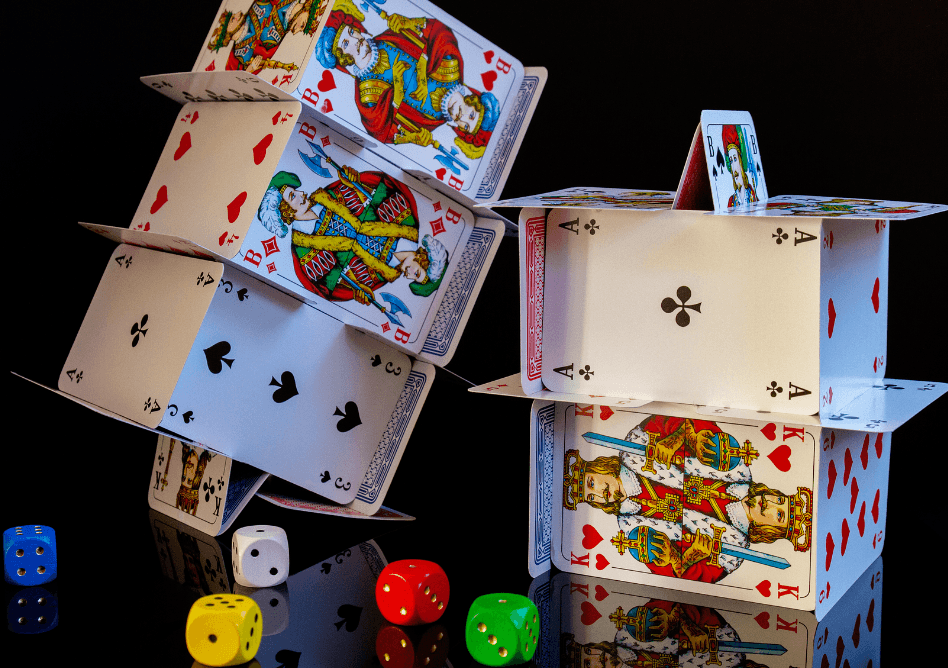 Two houses of cards stand behind a number of colorful dice.