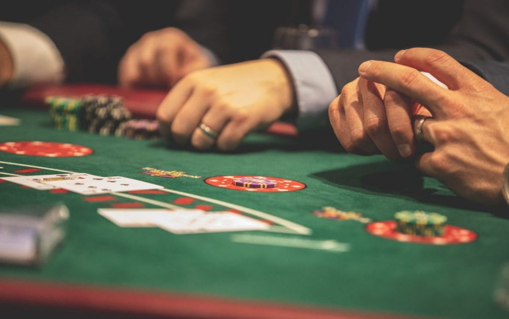 Poker players sit at a table and place bets with chips.
