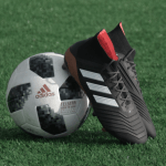 Football and football boots on green astroturf.