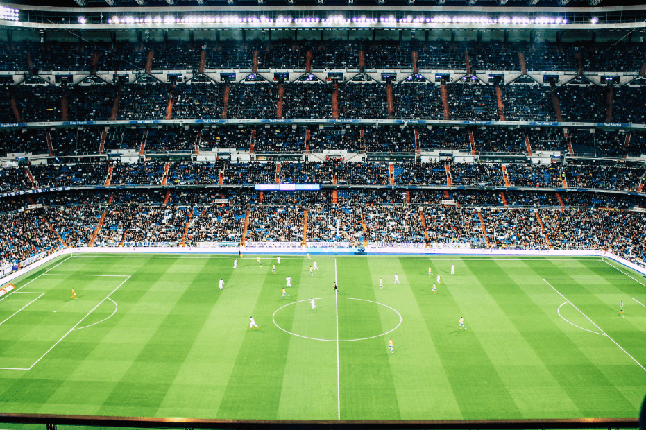A football stadium, with players on pitch and fans watching the match.