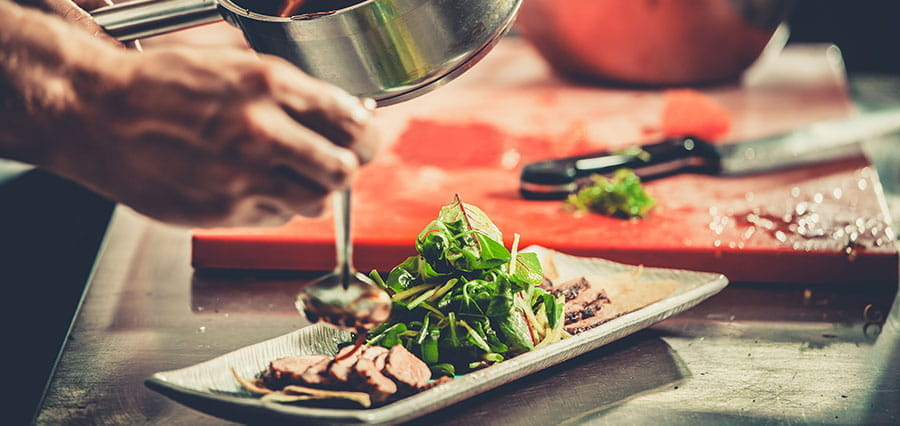A chef drizzling sauce over a plate of duck and salad.