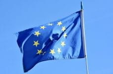 The flag of the European Union flying from a flagpole.