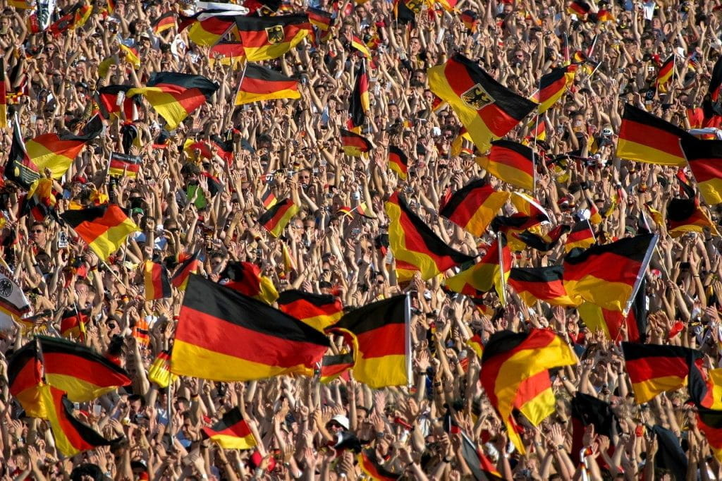 Many German flags being held by supporters at a football game.