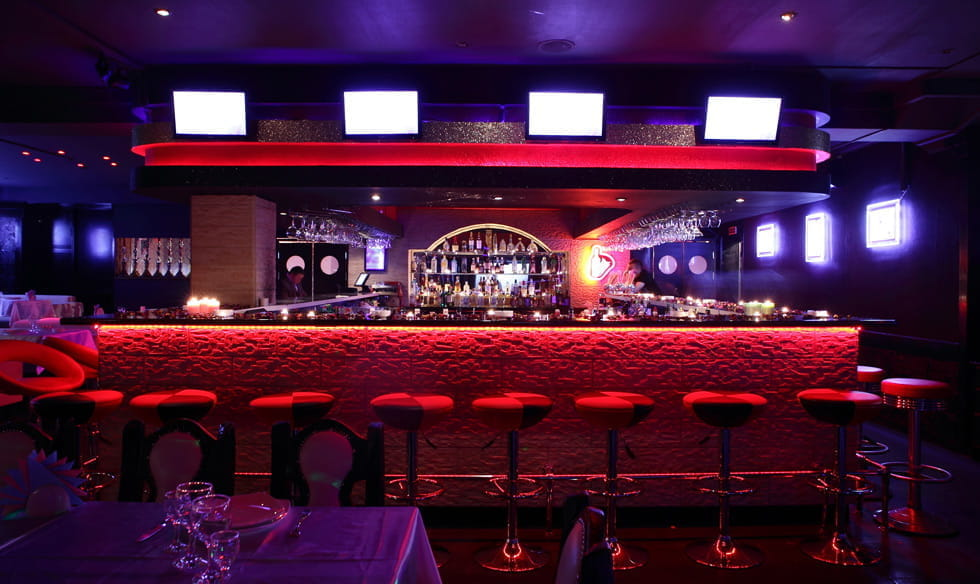 A fancy bar with red decor and purple lighting.