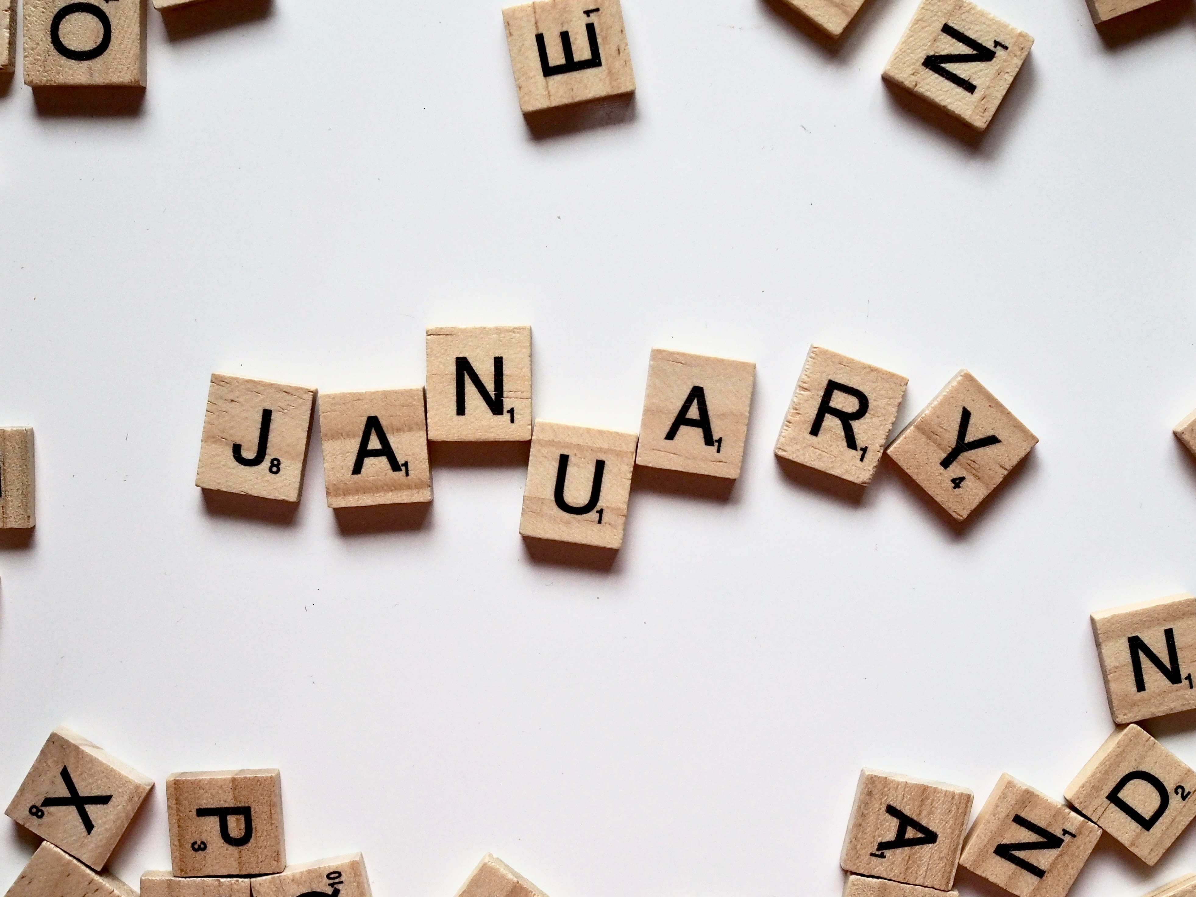 Wooden scrabble letters spell out of January against a white background.