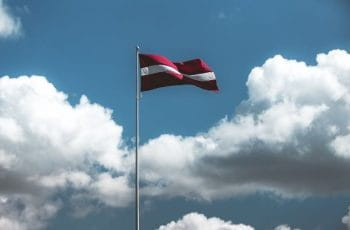 The Latvian flag flying from a flagpole with the sky in the background.