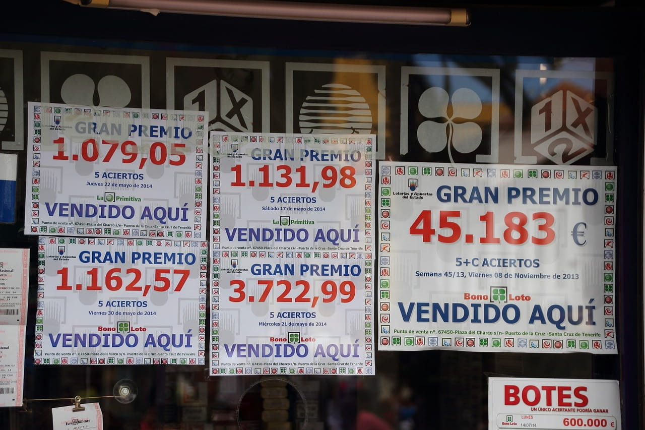 A window display with paper signs advertising lottery jackpots in Spanish.