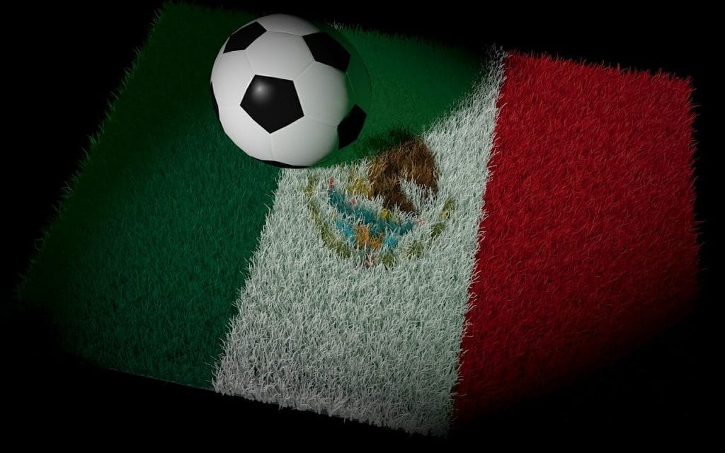 A soccer ball sits on a patch of grass illuminated in the design of Mexico's flag.
