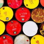 A colorful closeup of red, yellow, white, and brown barrels containing oil.
