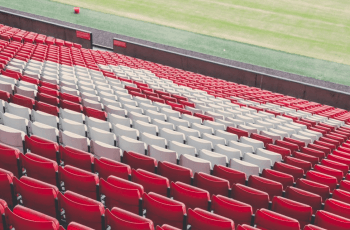 Red plastic seats in an empty football stadium.
