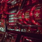 A close-up view of a row of slot machines, glowing red neon lights.