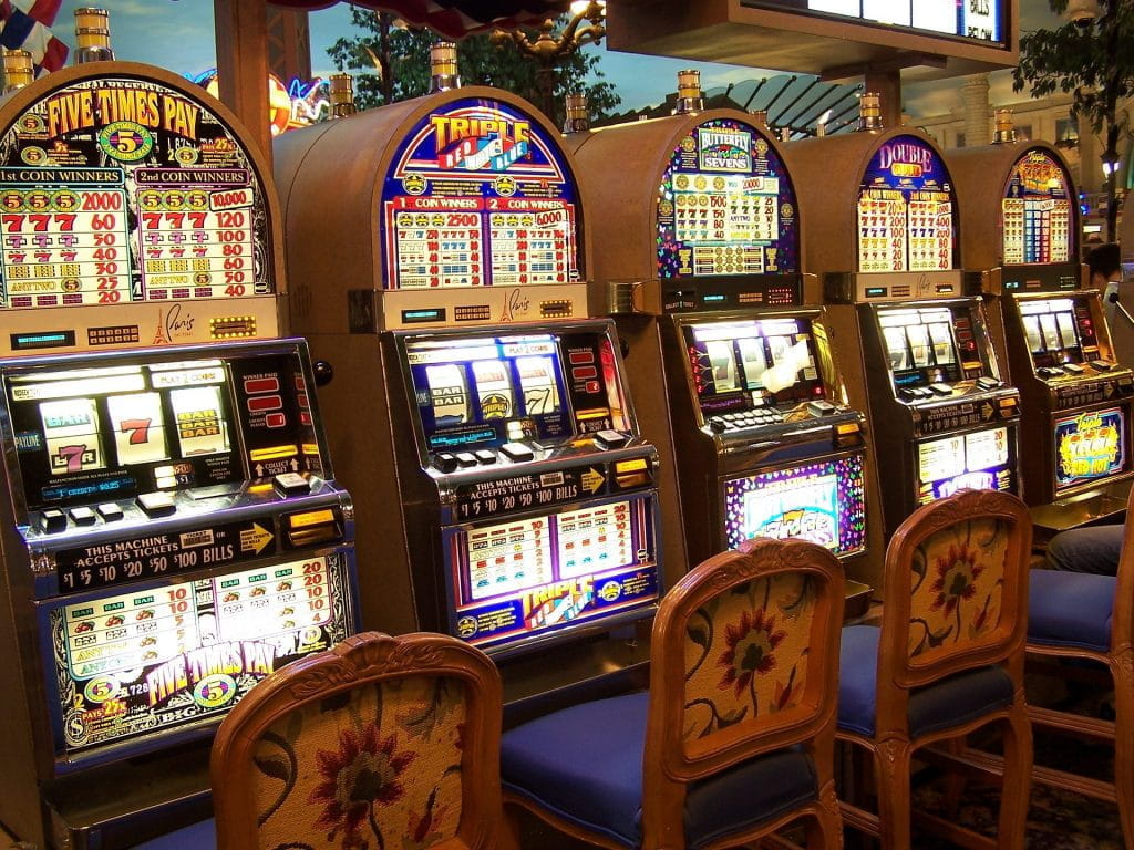A row of brightly lit slot machines in a casino.