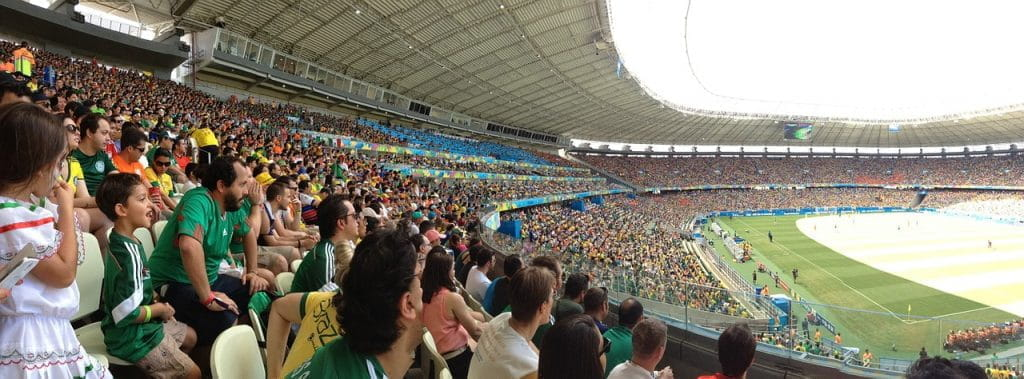 Soccer fans, many of whom wearing Mexico team jerseys, eagerly watch an ongoing soccer game at a stadium in the day.