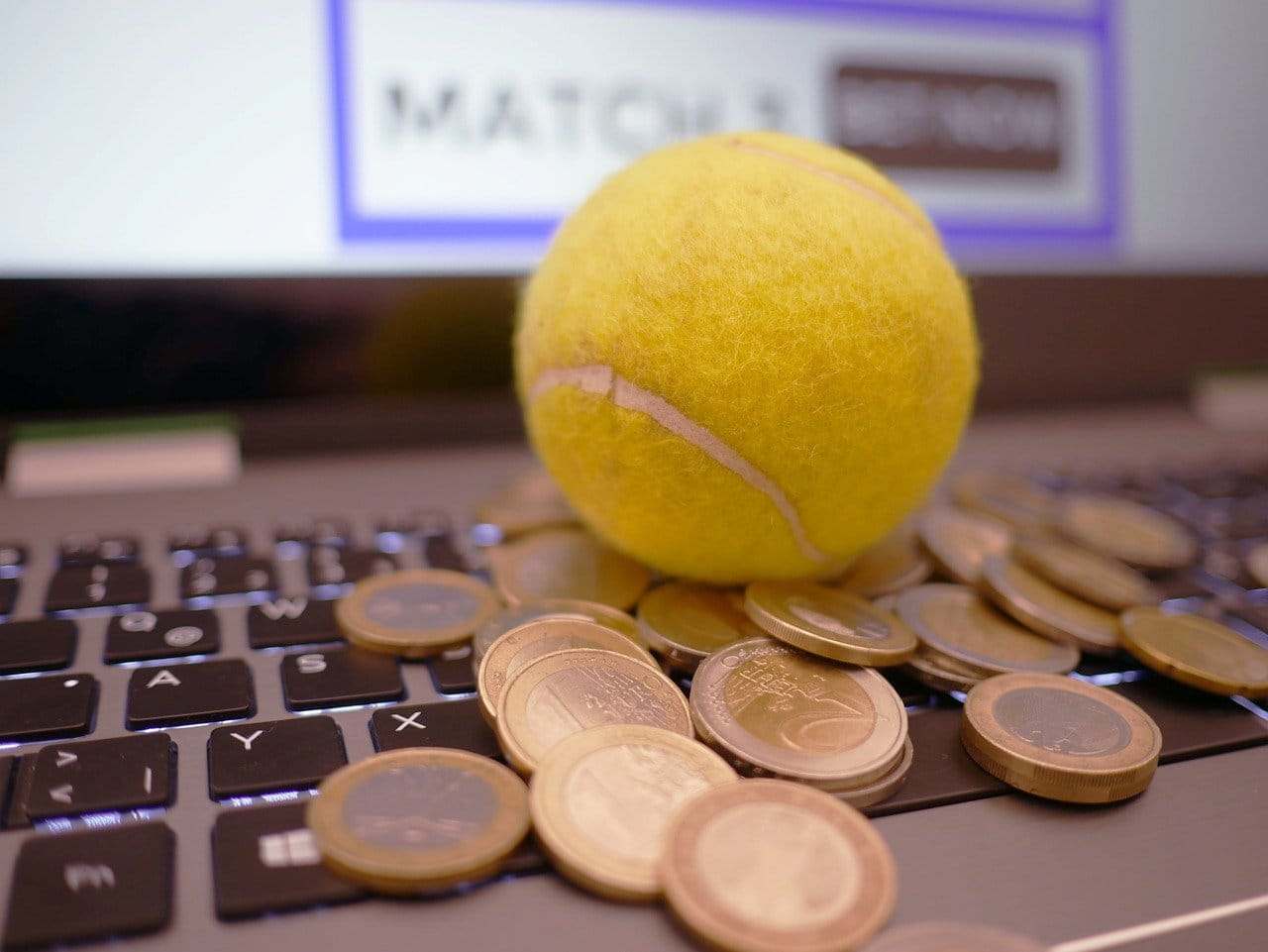 A tennis ball and a pile of euros resting on a computer keyboard.