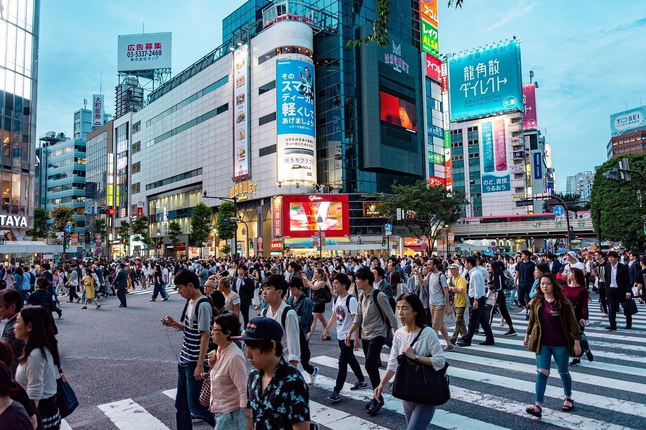 People crossing the road in Tokyo with billboards in the background.