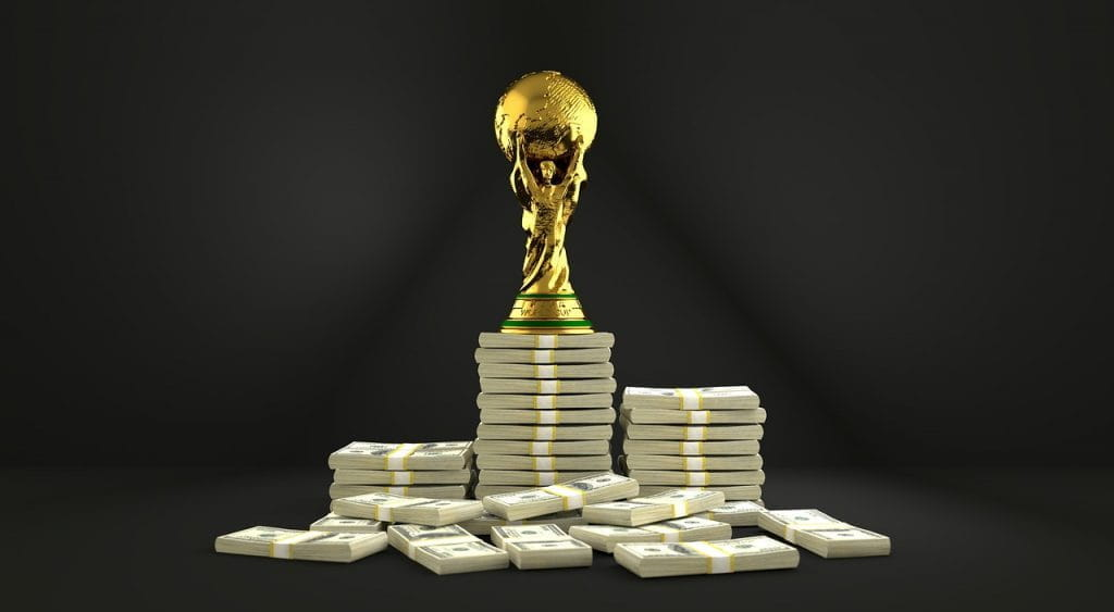 An image of a golden soccer trophy atop a large pile of money.