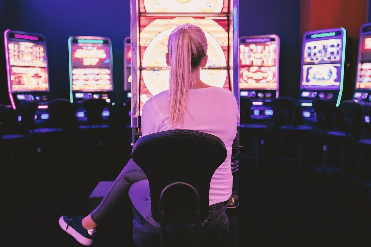 A woman sat at a slot machine in a casino.