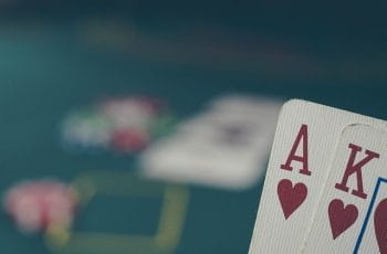 Ace-king of hearts in front of a poker table with chips on.