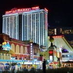 Atlantic City Boardwalk at night including lit up casinos.