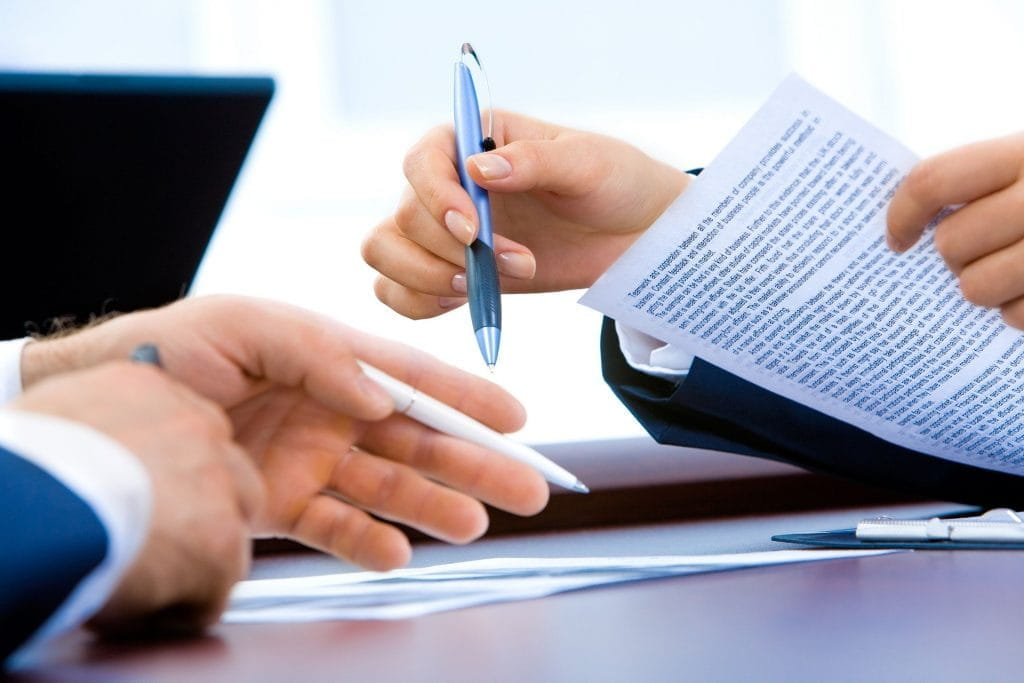 A business deal takes place with pens and documents.