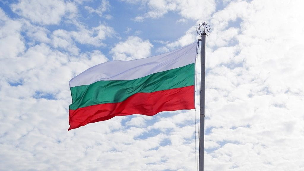 The Bulgarian flag flying from a flagpole.