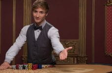 A casino croupier, offering a seat at his gaming table.