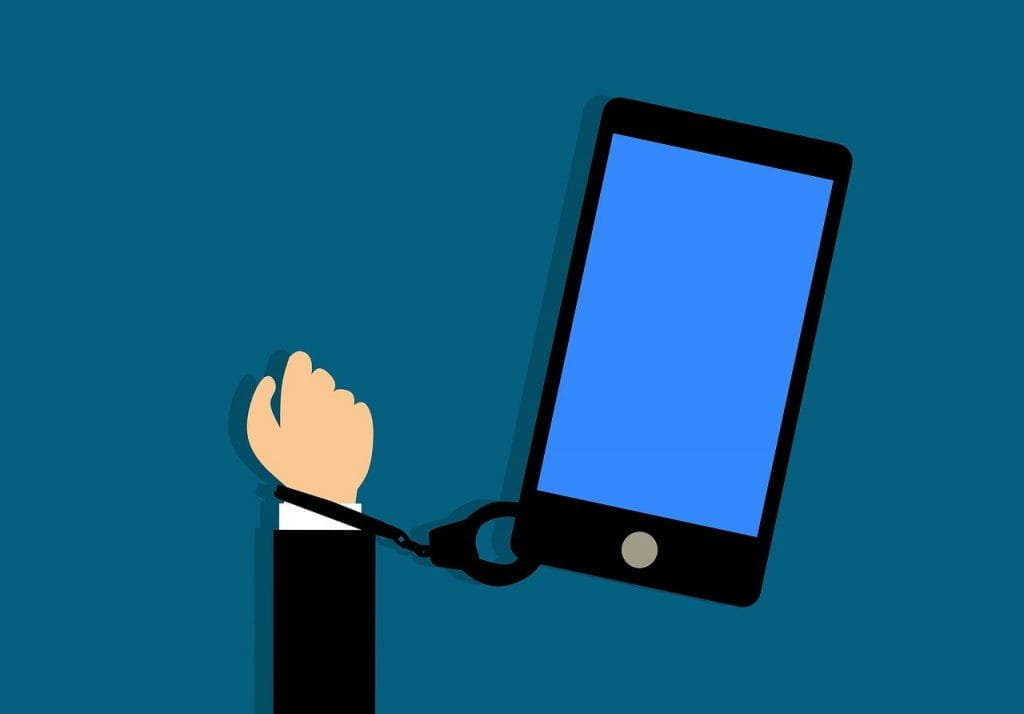 A white hand in a suit jacket handcuffed to a large smartphone.