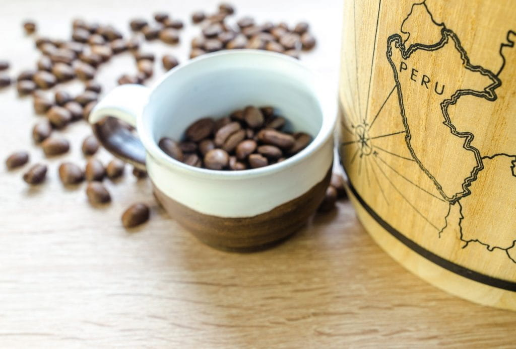 A small mug filled with coffee beans sits next to a map printed on wood that marks the location of Peru.