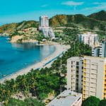 A sunny view of the coastline where buildings meet the beach in Colombia.