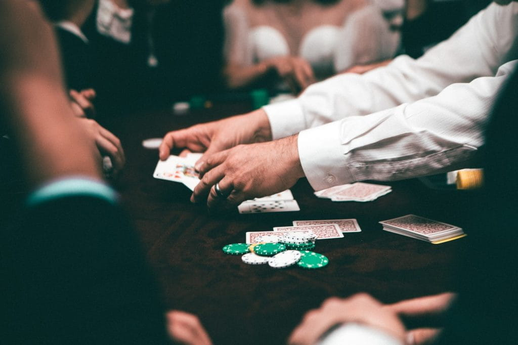 A look at a poker table, where a dealer in a white button-down shirt deals to players.
