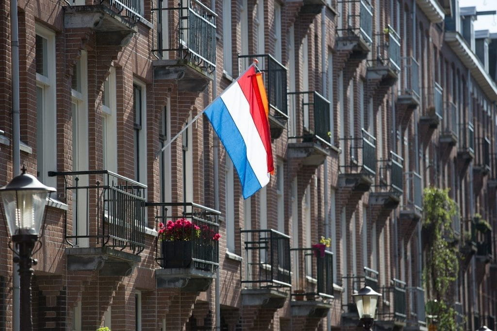 The Dutch flag hanging from a flag pole on a building.