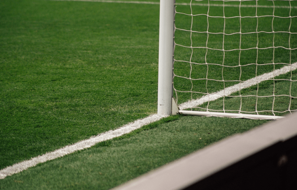 Edge of a football pitch with white markings and goal.