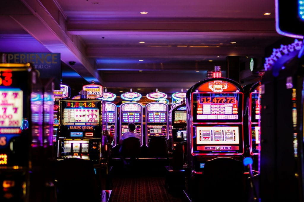 Slot machines glowing with neon lights on a casino floor.