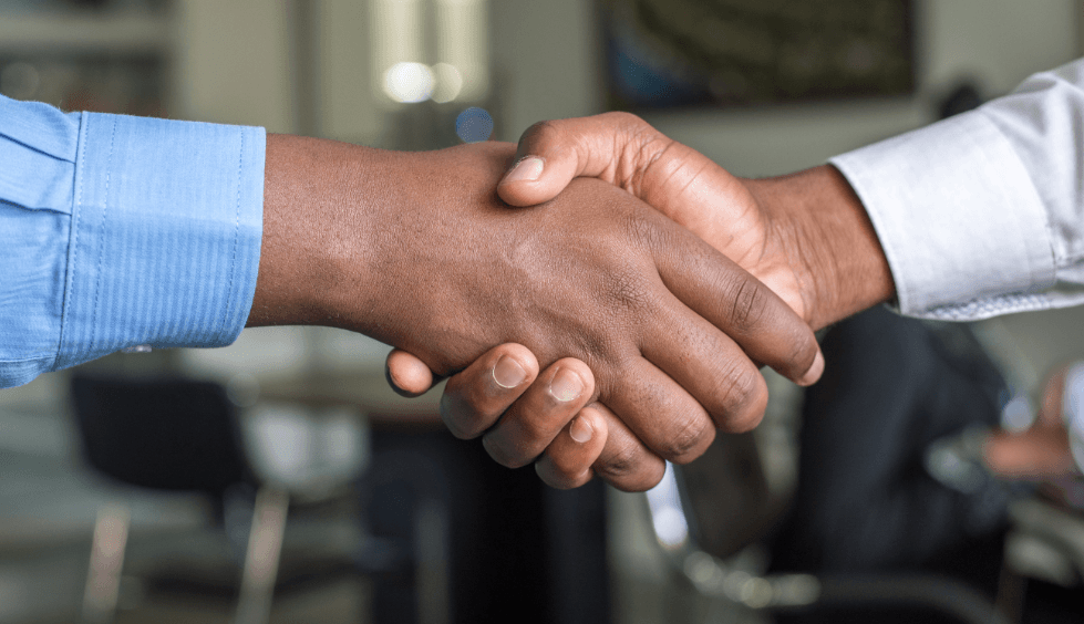A handshake between two hands, both Black, coming from long-sleeved work shirts.