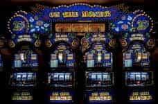 Three slot machines line an arcade wall.