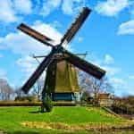 A Dutch windmill next to a house.