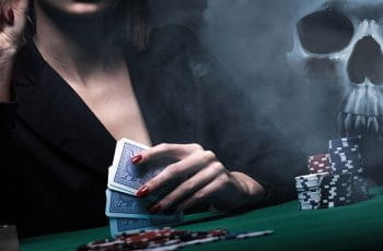 A woman holding playing cards, sitting at a gambling table, with a skull in the background.